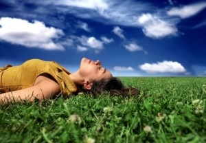 Woman lying on grass with bright blue sky and fluffy white clouds