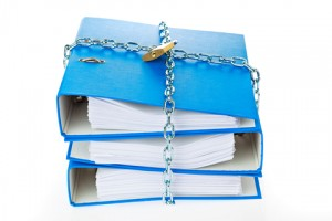 3 blue work binders piled on each other and locked together with lock