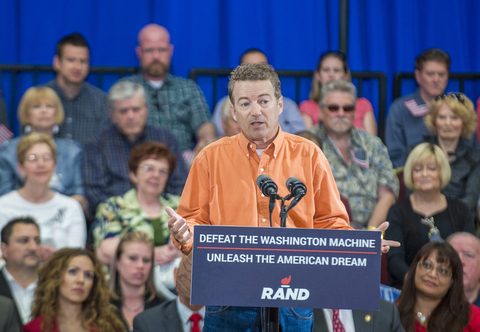 Rand Paul in prison orange colored shirt